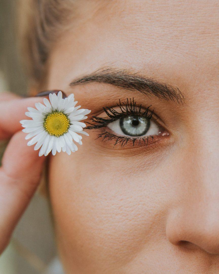 Frau hält weiße Blume neben ihr strahlendes Auge
